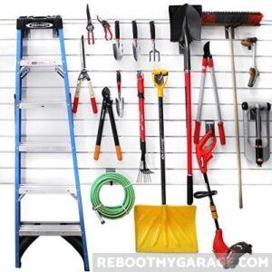 Proslat wall panel slatwall garage organization holding a ladder, hose, shovel, weed trimmer, and garden tools